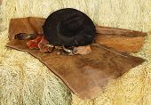 picture of brahma-bull  - Hat gloves spurs and chaps resting on hay bales - JPG