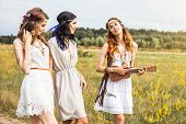 Three Beautiful Cheerful Hippie Girls, Outdoors, Trendy Hairstyles, Feathers In Her Hair, White Dres poster