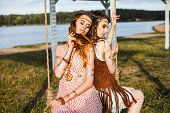 Two Cute Beautiful Hippie Girl In The Setting Sun, And Ride On A Swing, Outdoors, Best Friends, Feat poster