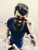 Man And Mustache Wears Sunglasses, Water Surface On Background. Hipster On Cheerful Face With Fashio poster