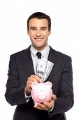 picture of holding money  - Businessman putting money in piggy bank - JPG