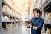 Young Asian Man Doing Stocktaking Of Product In Cardboard Box On Shelves In Warehouse By Using Digit poster