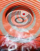 picture of smoke detector  - Illustration of a smoke and fire detector in gray and red in rising smoke at a ceiling - JPG