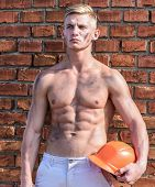 Builder With Muscular Torso And Helmet, Brick Wall Background. Athlete With Sexy Nude Torso With Har poster