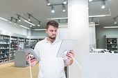 Handsome Man Stands In The Electronics Store With Two Tablets In His Hands And Chooses. Choose And B poster