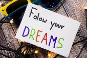 Follow Your Dreams Motivational Handwritten Message On Paper Above Retro Wooden Background With Ligh poster