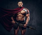 Brutal Ancient Greek Warrior With A Muscular Body In Battle Equipment Posing On A Dark Background. poster