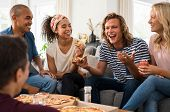 Group of multiethnic friends eating pizza during party at home. Group of young men and women having  poster