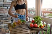 Young Woman With Perfect Abdominals Cooks Food In A Kitchen. She Has A Muscular Body And A Diet Food poster
