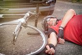 Cyclist lying on the road after an accident involving a car and a bicycle poster