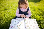 Moscow, Russia. 9 May, 2018. Adorable Little Girl Reading Botany Book, Learning Nature In The Garden poster