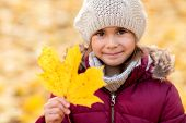 childhood, season and people concept - happy little girl with fallen maple leaf at autumn park poster