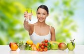 diet, healthy eating and people concept - woman with food on table drinking water over green natural poster
