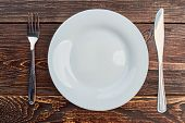 Table Setting With Plate, Fork And Knife. White Empty Plate, Silver Fork And Knife On Dark Wooden Ba poster