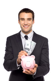 image of holding money  - Businessman putting money in piggy bank - JPG