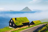 Foggy morning view of a house with typical turf-top grass roof in the Velbastadur village on Streymo poster