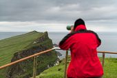 Foggy view of old lighthouse from viewpoint with tourist binoculars on the Mykines island, Faroe isl poster