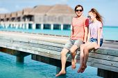Happy beautiful family of father and his teenage daughter outdoors on wooden jetty during summer vac poster