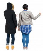 Back view of two young girl in winter jacket showing thumb up. Rear view people collection. backside poster