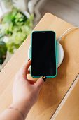 Smartphone In Mint Silicone Case Is Charged From A Wireless Charger. Smartphone In Hand. The Mobile  poster