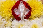 Face Of Lord Ganesha Placed Over Beautiful Rose And Chrysanthemum Flowers. Use For Religious Concept poster