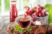 Grape Juice From Red Grapes In A Transparent Glass Glass With A Double Bottom. There Is A Basket Of  poster