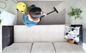 Young Woman Cleaning Carpet With Vacuum Cleaner At Home With Natural Light And Pastel Colored Furnit poster