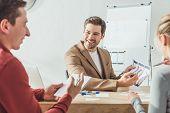 Selective Focus Of Smiling Designers Developing Mobile App Interface In Designer Studio poster