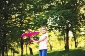 Little Girl Launches A Toy Plane Into The Air In The Park Outdoor. Child Launches A Toy Plane. Beaut poster