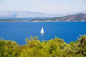 Picturesque Seascape. A Small White Boat On A Background Of Blue Sea And Mountains. poster