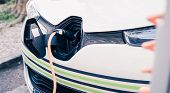 Charching An Electric Car With Power Cable Supply, Plugged In poster