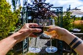 Hands Toasting Red And White Wine Glasses Selective Focus Close Up, In The Front Of A Winery Garden  poster