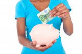stock photo of brazilian money  - Black african american woman inserting a euro bill inside a smiling Piggy bank isolated on white background  - JPG