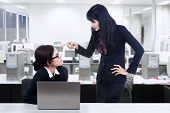 stock photo of annoying  - Businesswoman angry with her subordinate in the office - JPG