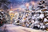 picture of ascension  - Church with illuminated Christmas trees in snowfall on Christmas eve in winter time - JPG