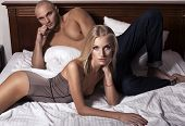 stock photo of silk lingerie  - sportive man with his beautiful girlfriend on bed - JPG