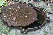 stock photo of manhole  - Open old and rusty manhole - JPG
