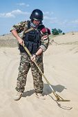 stock photo of landmines  - iraqi soldier in the desert with army metal detector - JPG