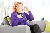 stock photo of asthma  - Mature woman seated on a sofa taking asthma treatment with inhaler at home - JPG