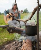 stock photo of boy scout  - tourists kettle on fire against song man - JPG