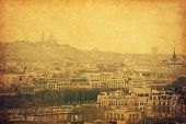 The view on the old part of Paris, the faraway Montmartre. Photo in retro style. Paper texture.