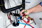 foto of clog  - Hands of professional Plumber with a wrench - JPG