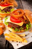 stock photo of beef-burger  - Beef burger with onion rings and french fries - JPG