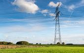 stock photo of dike  - Landscape in the Netherlands with high voltage cables one pole and a dike against a blue sky - JPG