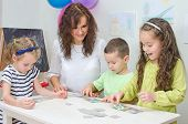 stock photo of child development  - Young teacher plays with children in kindergarten - JPG
