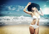 foto of indian beautiful people  - Beautiful young woman in bikini with black strw hat on the beach - JPG
