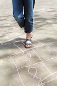 stock photo of hopscotch  - girl hopping in hopscotch outdoors in sunny day - JPG
