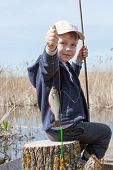 pic of caught  - Happy boy holding a fish caught in the pond - JPG