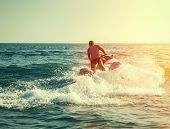 stock photo of jet-ski  - Silhouette of strong man jumps on the jetski above the water at sunset - JPG