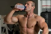 stock photo of pectorals  - Handsome Muscular Man Drinking Protein Drink In Gym - JPG